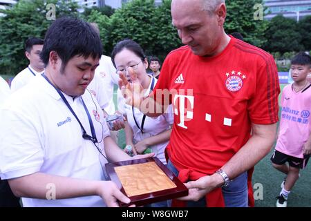 Former German soccer star Raimond Aumann, right, leaves his handprint during a fan meeting event in Guangzhou city, south China's Guangdong province, - Stock Photo