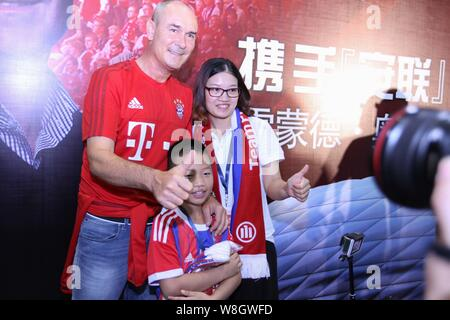 Former German soccer star Raimond Aumann, left, poses with Chinese fans during a fan meeting event in Guangzhou city, south China's Guangdong province - Stock Photo