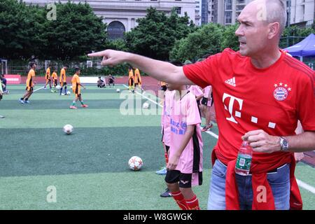 Former German soccer star Raimond Aumann, right, instructs students to play football during a fan meeting event in Guangzhou city, south China's Guang - Stock Photo