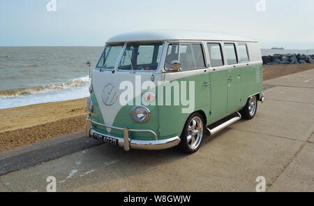 Classic Green and white  VW Camper Van parked on Seafront Promenade. - Stock Photo