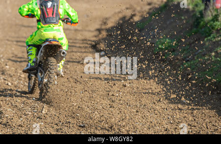 Unrecognized Athlete riding a sports motorbike and muddy wheel on a motocross racing event - Stock Photo