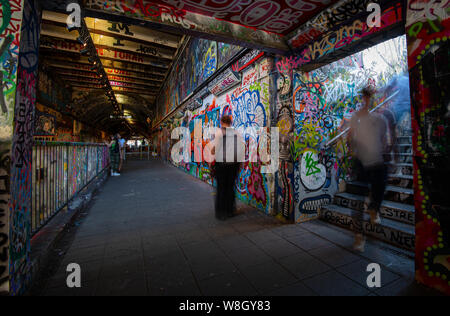 London, United Kingdom, July 04 2019: Graffiti by street artists and moving people at the famous Vaults of London at the Waterloo station - Stock Photo