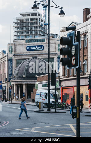 London, UK - July 16, 2019: People walking on a street in London in front of Brixton O2 Academy, one of Londons leading music venues, nightclubs and t - Stock Photo