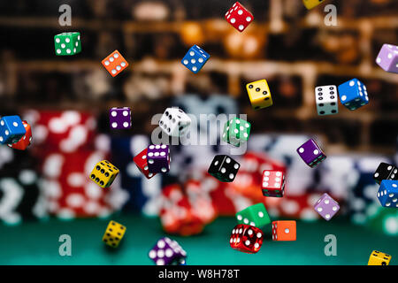 Multicolored dice Chips cascading in front of a background of stacked poker chips.  Depth of field is medium, so many dice are in focus and many other - Stock Photo
