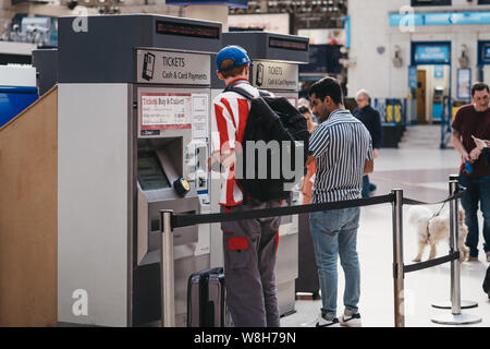 London, UK - July 16, 2019: People buying train tickets from a self-service machine inside Victoria train station, one of the busiest railway stations - Stock Photo