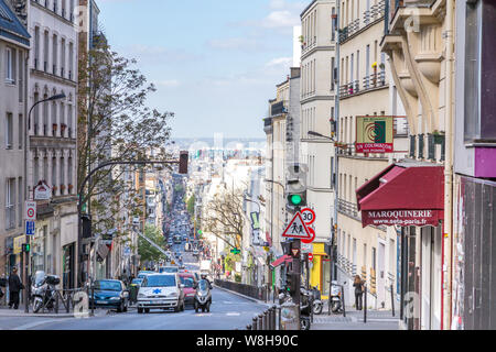 Paris, France - April 15, 2014: the Menilmontant Street (rue Menilmontant) at Paris with a few cars and people walkint. It is possible to see the Beau - Stock Photo