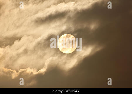 The disk of the sun shines through the clouds and fog. - Stock Photo