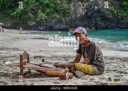 BALI, INDONESIA - JANUARY 14, 2018: Old man is playing a traditional balinese instrument gambang on White Sand Beach, Bali, Indonesia - Stock Photo