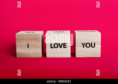 Message 'I love you spelled' in wooden blocks on pink background - Stock Photo