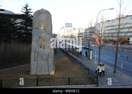 --FILE--Pedestrians walk past a signboard of Zhongguancun in Beijing, China, 31 January 2015.   Beijing's Zhongguancun, one of the country's leading t - Stock Photo