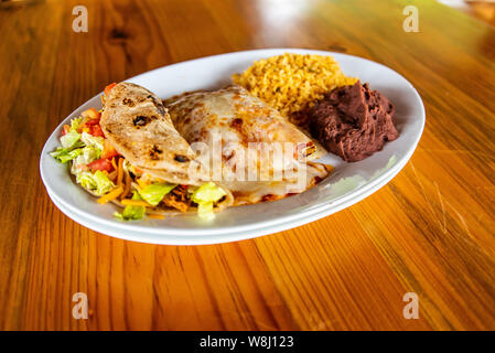 Chicken Enchilada plate with rice, beans and chicken taco - Stock Photo