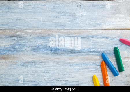 school children's concept. colored pencils and crayons on a blue and white scuffed vintage wooden background. the view from the top. Flat lay - Stock Photo