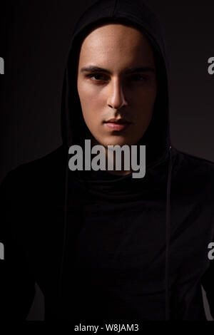 Mysterious angry man in black hoodie with hood on the head on dark background. Dangerous criminal person in the dark - Stock Photo