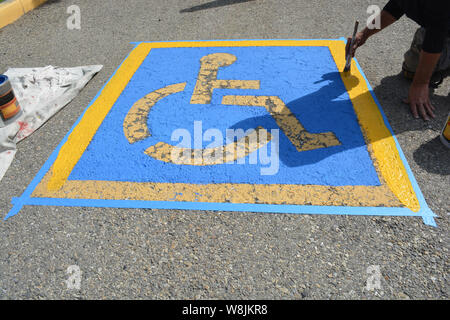 Painter repainting handicap parking on street pavement - Stock Photo