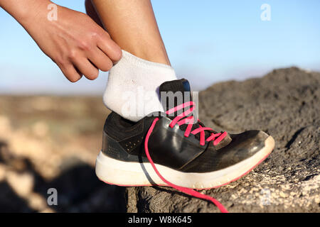 Runner putting on fitness shoes and running shoes closeup outdoors on mountain background. Female athlete getting ready for marathon race preparing her feet on trail run. - Stock Photo