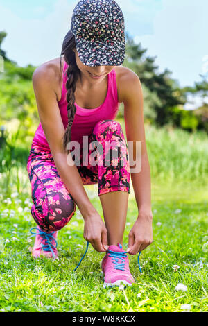 Cute sporty runner girl in fashion activewear wearing floral cap and pink leggings outfit getting ready for jogging tying laces running shoes on grass park. Fitness woman living active lifestyle. - Stock Photo