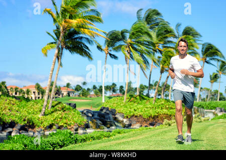 Active lifestyle man runner jogging in high end luxury residential american tropical neighborhood - Miami Florida living. Healthy running male fitness athlete working out cardio on grass in summer. - Stock Photo