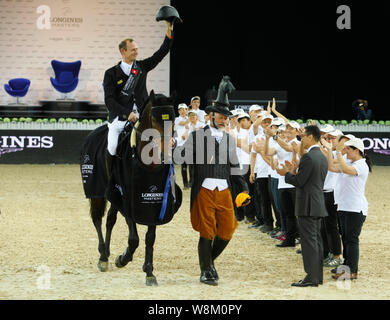 Macro Kutscher of Germany, top, waves on his horse Van Gogh after winning the show jumping Longines Masters Grand Prix during the award ceremony  in H - Stock Photo