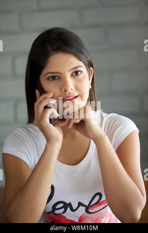 Young woman talking on a mobile phone in a restaurant - Stock Photo