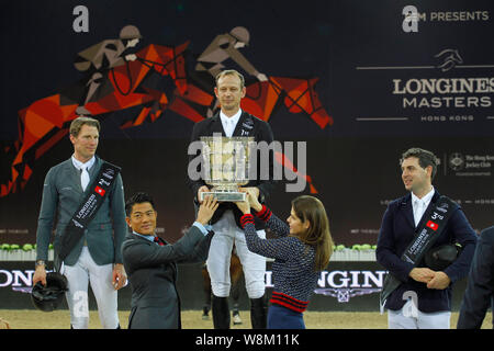 Macro Kutscher of Germany, top, is awarded a trophy by Hong Kong singer and actor Aaron Kowk, front left, after winning the show jumping Longines Mast - Stock Photo