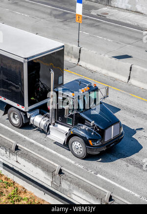 Shiny Black professional industrial grade big rig day cab semi truck for local deliveries transporting black dry van semi trailer with commercial carg - Stock Photo