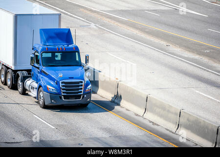 Shiny Blue professional industrial grade big rig day cab semi truck for local deliveries transporting hard dry van semi trailer with commercial cargo - Stock Photo