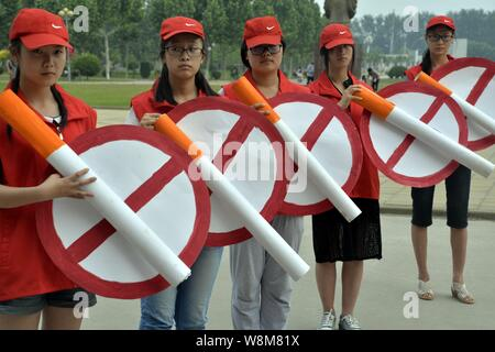 --FILE--College students hold large paper cigarettes and No-smoking signs at an anti-smoking campaign before World No Tobacco Day at a university in L - Stock Photo
