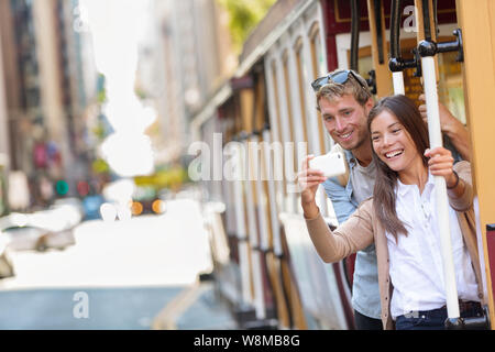 Couple tourists riding the popular touristic attraction cable car system in San Francisco city, California during summer travel holidays. People having fun taking selfie picture and tourist photos. - Stock Photo