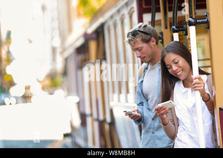 San Francisco cable car tourists people texting using mobile phone smartphone app on railway tram ride outside in urban city street. Summer travel destination tourism, couple on public transport. - Stock Photo