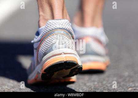 Running shoe closeup of man running on road with sports shoes. Road to success. Runner training cardio exercising, walking or start of run on marathon race road. Feet health, heel care. - Stock Photo