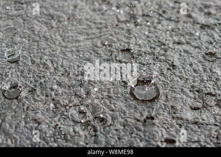 rain gray background. Drops on a puddle. - Stock Photo