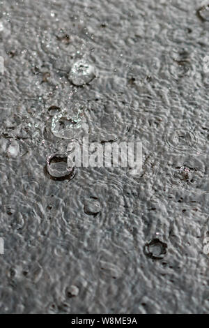 rain gray background. Drops on a puddle. Vertical photo. - Stock Photo