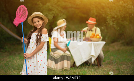 A Cute Dark-haired Girl In A Sundress With A Pink Butterfly Net. - Stock Photo