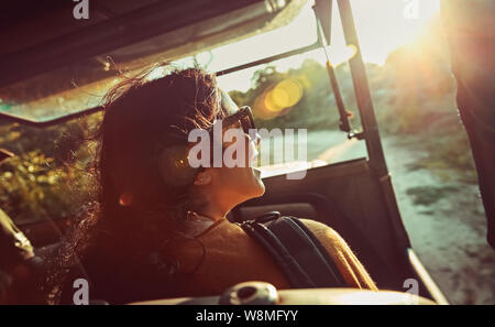 Happy woman on safari ride, pretty female enjoying trip along Sri Lanka, riding on a special convertible car and admires view on wild animals - Stock Photo
