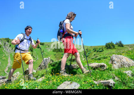 Couple hiking in the austrian alps - Stock Photo