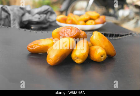 close up of fresh riped delicious  yellow dates  on black background. - Stock Photo