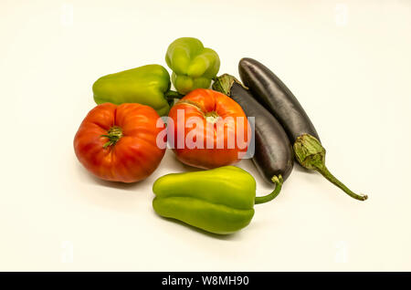 A group of fresh vegetables from green sweet peppers and  large red tomatoes and black- purple eggplants grown in Armenia lies on a white background - Stock Photo