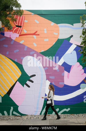 Vancouver, Canada. 9th Aug, 2019. A woman passes by a new mural on the street during the 4th annual Vancouver Mural Festival in Vancouver, Canada, Aug. 9, 2019. The festival returns for its fourth year showcasing over 100 pieces of mural artworks with 25 pieces newly added this year painted by famous street artists from around the world. Credit: Xinhua/Alamy Live News - Stock Photo