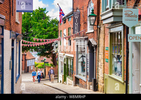 2 July 2019: Lincoln, UK - Steep Hill, the city's famous historic street, with independent shops, cafes and tourists walking up the hill. - Stock Photo