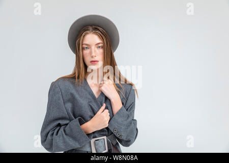 Portrait of young freckled woman in grey hay and coat isolated white background copyspace - Stock Photo