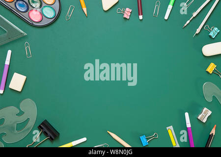 School supplies on green chalkboard  background - top view - Stock Photo