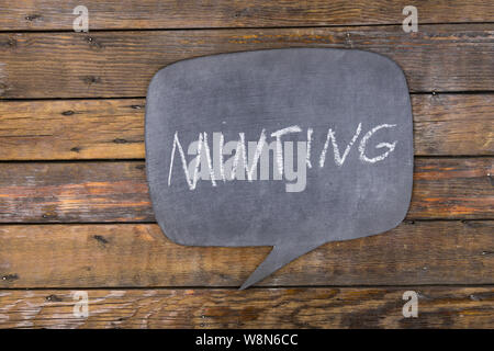 Word, inscription MINTING written in chalk on a blackboard made in the form of thought. Top view. - Stock Photo