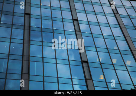 part of the facade of a glass skyscraper. Modern architectural background of the city. Business center background - Stock Photo