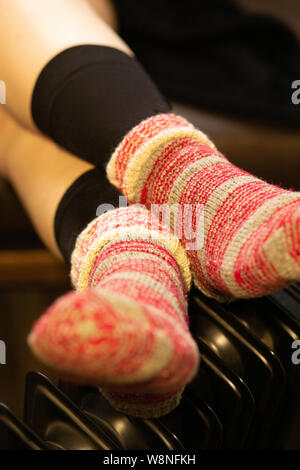 female legs in knitted socks on a warm radiator closeup view - Stock Photo