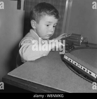 1950s, historical, smartly dressed little boy wearing a bow tie playing with his electric model train set, Engalnd, UK. - Stock Photo