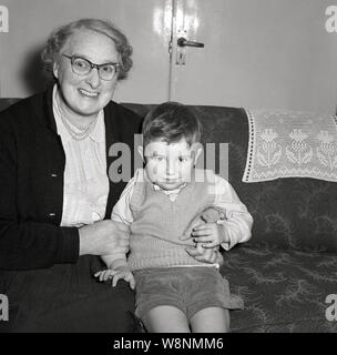 1950s, historical, smartly dressed little boy sitting indoors on a sofa with his Grandmother, England, UK. - Stock Photo