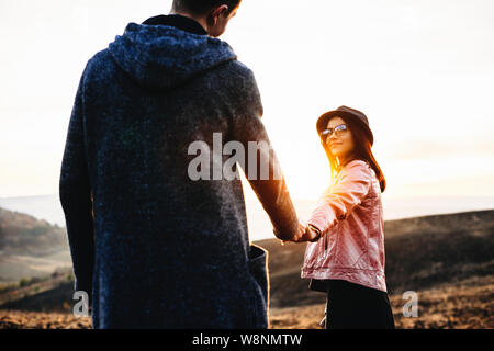 Pretty young lady smiling and holding hand of unrecognizable boyfriend while walking with him in meadow during amazing sundown.Young woman leading boy - Stock Photo