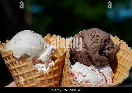 Different Flavors (Chocolate, Vanilla, Strawberry) Ice Cream scoops in homemade wide mouth crispy waffle cones. - Stock Photo