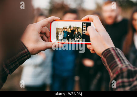 Hands of anonymous male using smartphone to take photo of group of young friends in nature. Crop hands taking picture of friends - Stock Photo