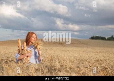 Redhead woman with bakery products in ripe wheat field - Stock Photo